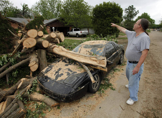 A compact car is uncovered in the street on Saturday, April 14, 2012, in Norman, Okla.  This resident of Nancy Linn Terrace (who did not want his name published) says strangers showed up right after Friday's tornado to help cut limbs from the giant tree that blew down and hit his brother's car.  Photo by Steve Sisney, The Oklahoman
