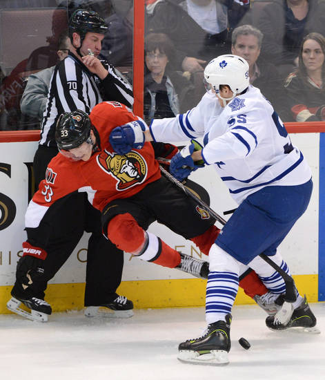 Ottawa Senators' Jakob Silfverberg gets hit by Toronto Maple Leafs' Korbinian Holzer during the second period of an NHL hockey game in Ottawa, Ontario, on Saturday, Feb. 23, 2013. (AP Photo/The Canadian Press, Sean Kilpatrick)