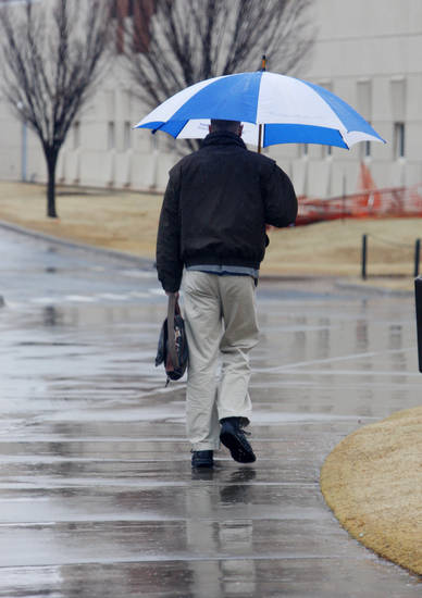 A pedestrian walking in the rain on the University of Central Oklahoma campus in Edmond Monday, Feb. 25, 2013.  Photo by Paul B. Southerland, The Oklahoman