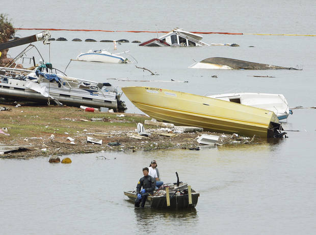 A salvage diver moves into position to recover boats and debris Wednesday. PHOTOS BY STEVE SISNEY, THE OKLAHOMAN