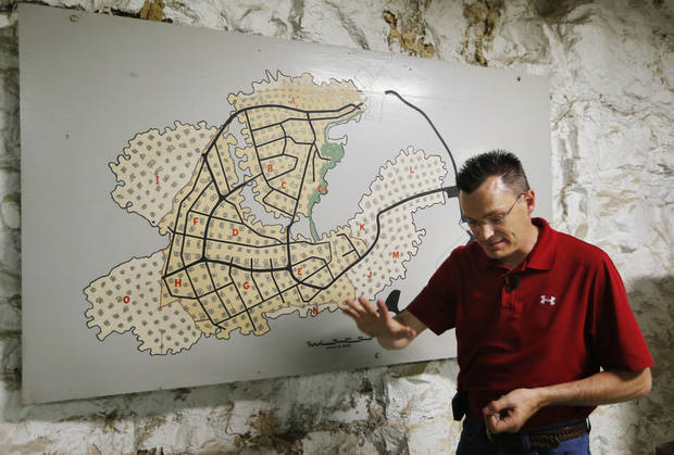Coby Cullins stands next to a map of the Vivos Shelter and Resort during a tour of the facility in Atchison, Kan., Tuesday, June 18, 2013. (AP Photo/Orlin Wagner)
