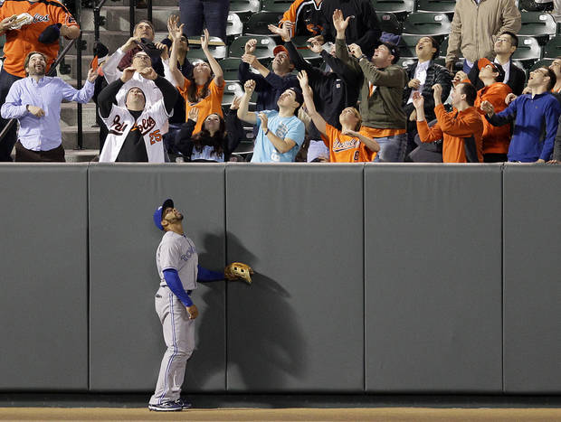 Toronto Blue Jays left fielder Eric Thames watches as fans reach for a solo home run ball hit by Baltimore Orioles' Chris Davis in the fourth inning of a baseball game in Baltimore, Wednesday, April 25, 2012. (AP Photo/Patrick Semansky)