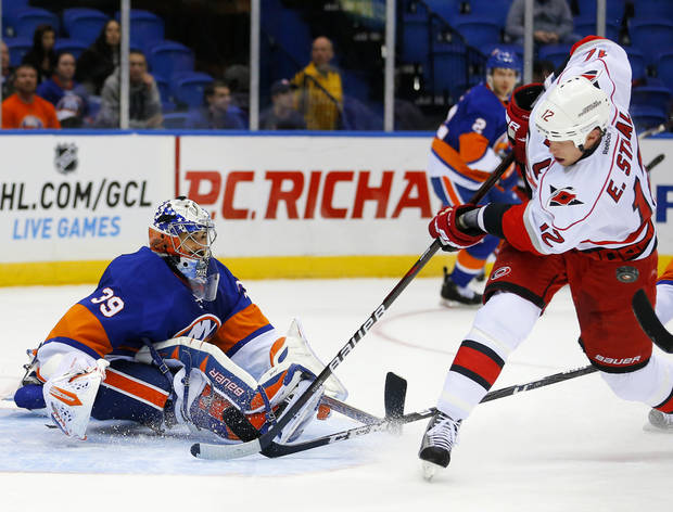 New York Islanders goalie Rick DiPietro (39) makes a save off Carolina Hurricanes center Eric Staal (12) during the first period of an NHL hockey game at the Nassau Coliseum in Uniondale, N.Y., Monday, Feb.11, 2013. (AP Photo/Paul J. Bereswill)