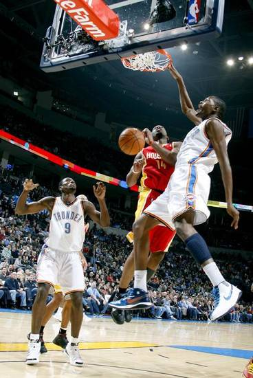 Oklahoma City's Kevin Durant (35) dunks the ball over Houston's Carl Landry (14) during the NBA basketball game between the Oklahoma City Thunder and Houston Rockets, Sunday, Nov. 29, 2009, at  the Ford Center in Oklahoma City. Photo by Sarah Phipps, The Oklahoman ORG XMIT: KOD