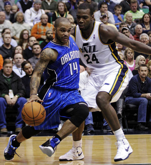 Orlando Magic point guard Jameer Nelson (14) drives to the basket as Utah Jazz power forward Paul Millsap (24) defends in the second quarter of an NBA basketball game, Wednesday, Dec. 5, 2012, in Salt Lake City. (AP Photo/Rick Bowmer)