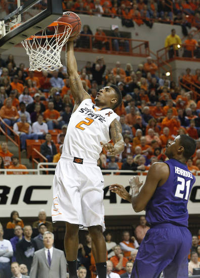 Oklahoma State guard Le'Bryan Nash (2) goes up for a dunk in front of Kansas State forward Jordan Henriquez (21) in the first half of an NCAA college basketball game in Stillwater, Okla., Saturday, March 9, 2013. Oklahoma State won 76-70. (AP Photo/Sue Ogrocki)