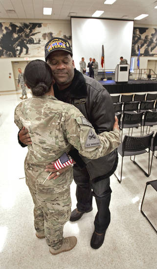 Willie Lloyd III greets his wife Sgt. Jo Del Lloyd as she and other members of the Oklahoma National Guard return from Afghanistan on Thursday, Jan. 12, 2012, in Norman, Okla.  