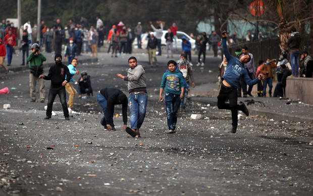 Egyptian protesters clash with riot police, not seen, near Tahrir Square, Cairo, Egypt,Tuesday, Jan. 29, 2013. Intense fighting for days around central Tahrir Square engulfed two landmark hotels and forced the U.S. Embassy to suspend public services on Tuesday. (AP Photo/Khalil Hamra)