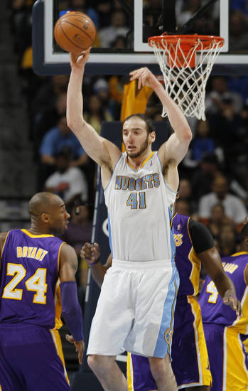 Denver Nuggets center Kosta Koufos, center, pulls down a rebound while covered by Los Angeles Lakers guard Kobe Bryant, front, and center Dwight Howard in the first quarter of an NBA basketball game in Denver on Monday, Feb. 25, 2013. (AP Photo/David Zalubowski)