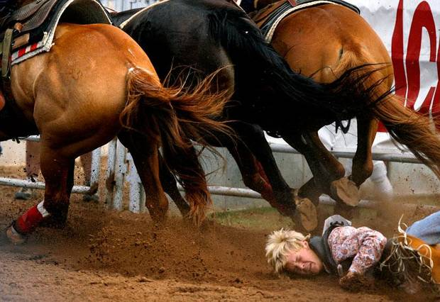 Stetson Cravens of Eufaula, Okla., falls to the ground after being dragged by a bucking bronc during the bareback bronc at the International Finals Youth Rodeo in Shawnee, Okla. Thursday, July 16, 2009.  Photo by Ashley McKee, The Oklahoman