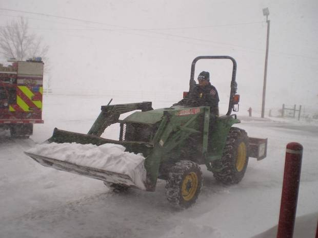 Deer Creek firefighters clear snow from drive in front of fire station so trucks can respond to calls in this wintry weather.  Submitted by Eric Harlow.