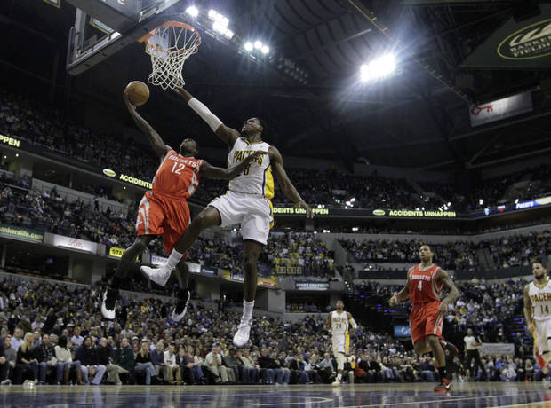 Houston Rockets' Patrick Beverley (12) has his shot blocked by Indiana Pacers' Ian Mahinmi (28) during the first half of an NBA basketball game Friday, Jan. 18, 2013, in Indianapolis. (AP Photo/Darron Cummings)