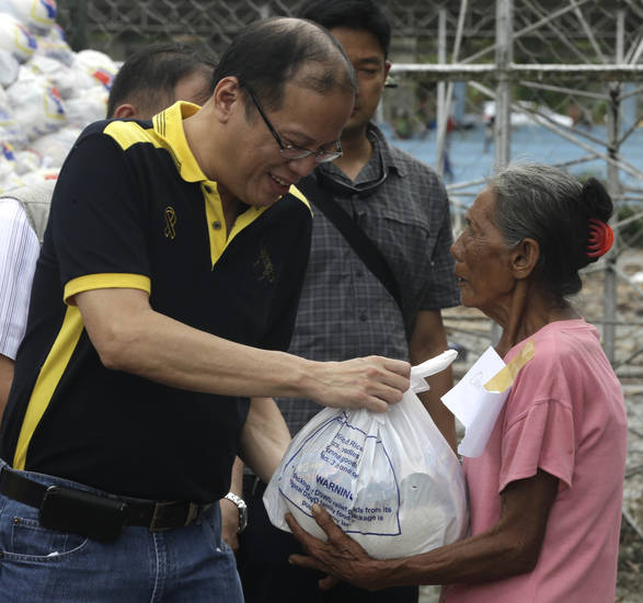 Philippine President Benigno Aquino III helps to distribute relief goods to a victim of Typhoon Bopha during his visit to New Bataan township, Compostela Valley in southern Philippines Friday Dec. 7, 2012. Rescuers were digging through mud and debris Friday to retrieve more bodies strewn across the farming valley by the powerful typhoon. (AP Photo/Bullit Marquez)