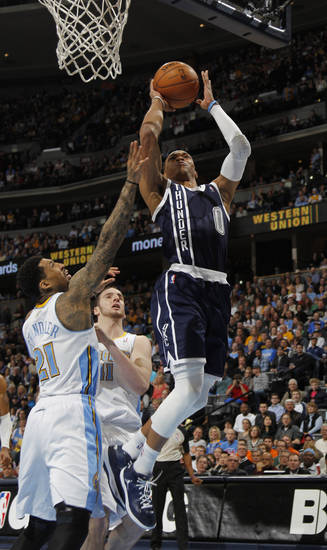 Oklahoma City Thunder guard Russelll Westbrook, right, goes up for a shot past Denver Nuggets forward Wilson Chandler, left, and center Kosta Koufos in the first quarter of an NBA basketball game in Denver on Friday, March 1, 2013. (AP Photo/David Zalubowski) ORG XMIT: CODZ108