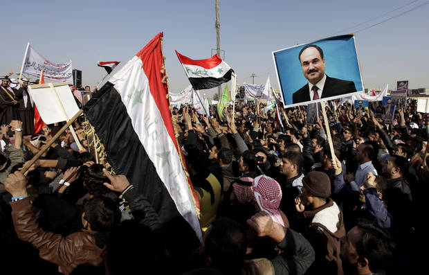 Protesters chant slogans against the Iraq's Shiite-led government as they wave national flags and hold posters of the Sunni Finance Minister Rafia al-Issawi during a demonstration in Fallujah, 40 miles (65 kilometers) west of Baghdad, Iraq, Sunday, Dec. 23, 2012. Thousands of protesters have demonstrated in Iraq's western Sunni heartland following the arrest of bodyguards assigned to the finance minister, who draws support from the area. (AP Photo/ Khalid Mohammed)
