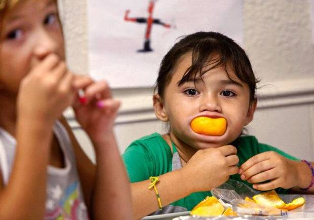 Miracle Medrano, 7, enjoys an orange slice, while a friend, Cristal (cq) Ramirez, 8, also enjoys an orange.  <strong>JIM BECKEL - THE OKLAHOMAN</strong>