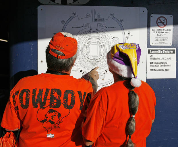 OSU fans Clay Kemp, left, and his wife, Sue Kemp, of Moore, Okla., check the location of their seats before the Holiday Bowl college football game between Oklahoma State and Oregon at Qualcomm Stadium in San Diego, Tuesday, Dec. 30, 2008. PHOTO BY NATE BILLINGS, THE OKLAHOMAN