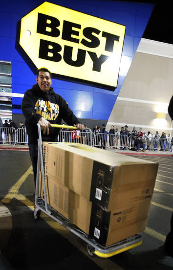 Romero Maya leaves with his purchase as shoppers enter Best Buy on Interstate 240 for Black Friday Sales on Friday, Nov. 23, 2012, in Oklahoma City, Okla.  Photo by Steve Sisney, The Oklahoman