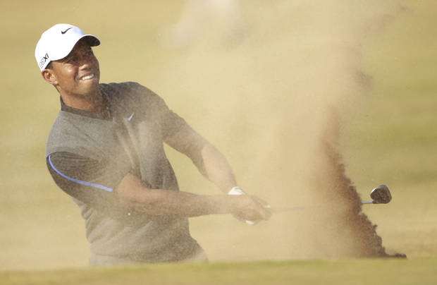 Tiger Woods of the United States plays out of  a bunker onto the 14th green during the third round of the British Open Golf Championship at Muirfield, Scotland, Saturday July 20, 2013. (AP Photo/Peter Morrison)