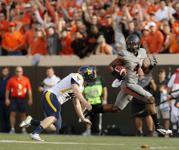 Oklahoma State&#039;s Justin Gilbert (4) gets past West Virginia&#039;s Corey Smith (44) on a kickoff return for a touchdown in the first quarter during a college football game between Oklahoma State University (OSU) and West Virginia University (WVU) at Boone Pickens Stadium in Stillwater, Okla., Saturday, Nov. 10, 2012. Photo by Nate Billings, The Oklahoman