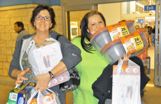Susan Walno and Jessica Flick, of Elk City, carry armloads of bargains out of the Elk City Walmart, which launched its Black Friday sales at 10 p.m. Thursday. Hundreds of shoppers crowded into the store, waiting in long lines for toys and electronics. <strong>JIM STAFFORD</strong>