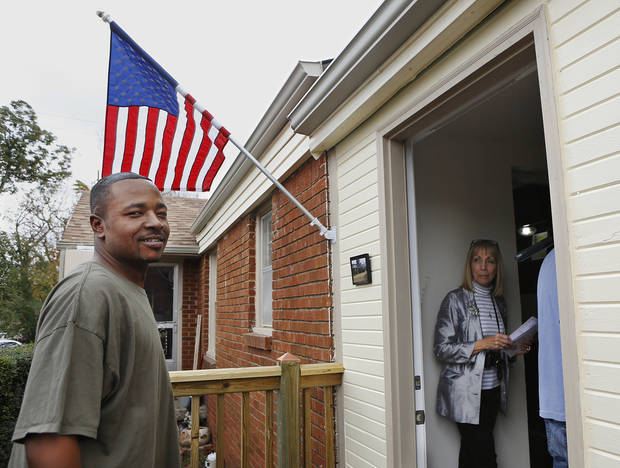 Deric Isaac, left, stands on his front porch as he enters his home for the start of the ceremony. <strong>Jim Beckel - THE OKLAHOMAN</strong>