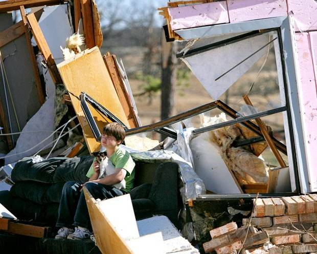 Deric Brawley, 12, sits with his dog on a friend's couch inside their destroyed home following deadly storms around Lone Grove, Okla., Feb. 11, 2009. By John Clanton, The Oklahoman