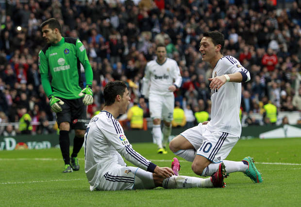 Real Madrid's Cristiano Ronaldo from Portugal, second left, celebrates his goal with Mesut Ozil from Germany, right, during a Spanish La Liga soccer match against Getafe at the Santiago Bernabeu stadium in Madrid, Spain, Sunday, Jan. 27, 2013. (AP Photo/Andres Kudacki)