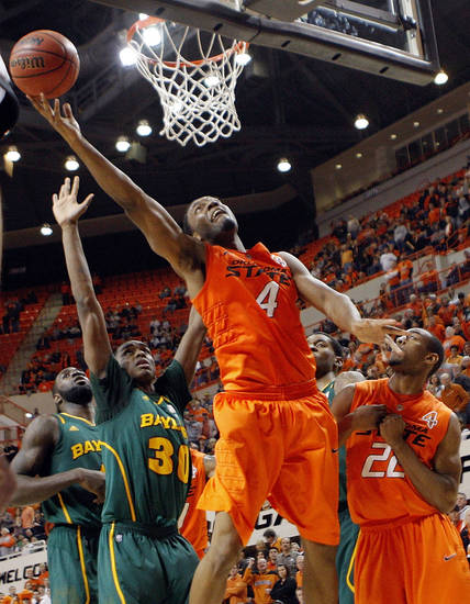 OSU's Brian Williams (4) takes a shot in front of Baylor's Quincy Acy (4), left, and Quicy Miller (30) as well as OSU's Markel Brown (22) in the second half of a men's college basketball game between the Oklahoma State University Cowboys and the Baylor University Bears at Gallagher-Iba Arena in Stillwater, Okla., Saturday, Feb. 4, 2012. Baylor beat OSU, 64-60. Photo by Nate Billings, The Oklahoman