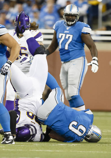 Detroit Lions quarterback Matthew Stafford (9) is sack by Minnesota Vikings defensive tackle Letroy Guion (98) during the first half at Ford Field in Detroit, Sunday, Sept. 30, 2012. (AP Photo/Rick Osentoski)