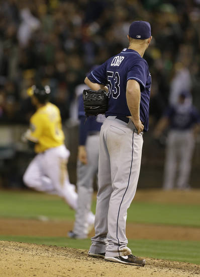 Tampa Bay Rays starting pitcher Alex Cobb, right, stands on the mound after giving up a home run to the Oakland Athletics' Coco Crisp during the eighth inning of their baseball game Saturday, Aug. 31, 2013, in Oakland, Calif. Oakland won the game 2-1. (AP Photo/Eric Risberg)