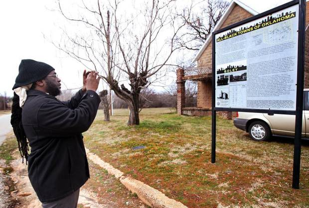 The Oklahoma Historical Society�s All-Black Towns Project includes placing markers in 13 surviving towns, including this one in Boley, where Langston University Marching Pride Band Director Larry Birden takes a photo of the sign in this file photo. PHOTO BY CORY YOUNG, TULSA WORLD