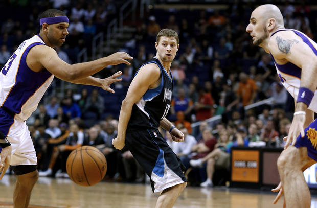 Minnesota Timberwolves' Luke Ridnour (13) passes between Phoenix Suns' Jared Dudley, left, and Marcin Gortat, of Poland, during the first half of an NBA basketball game, Tuesday, Feb. 26, 2013, in Phoenix. (AP Photo/Matt York)