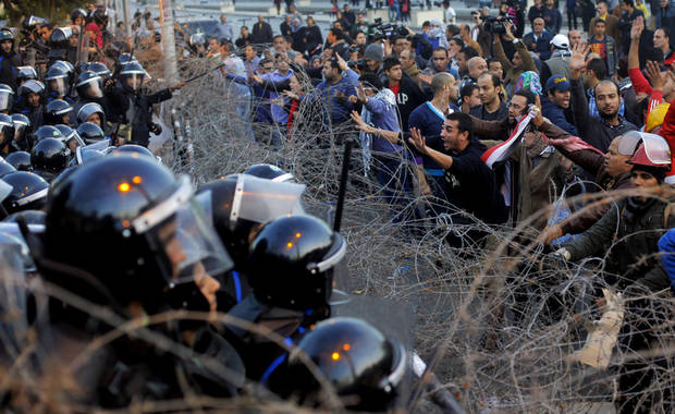 An Egyptian protester shouts to anti-riot soldiers in front of the presidential palace in Cairo, Egypt, Friday, Jan. 25, 2013. Two years after Egypt's revolution began, the country's schism was on display Friday as the mainly liberal and secular opposition held rallies saying the goals of the pro-democracy uprising have not been met and denouncing Islamist President Mohammed Morsi. (AP Photo/Amr Nabil) ORG XMIT: AMR115