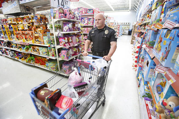 Oklahoma County sheriff�s deputy James Palmer pushes a cart full of toys for underprivileged children in the metro.