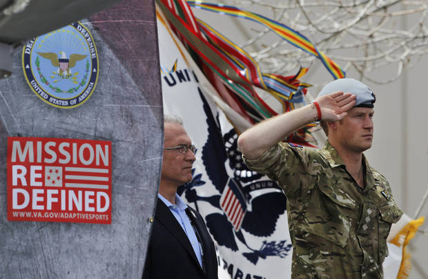 Britain's Prince Harry salutes during the opening ceremony for the 2013 Warrior Games, at the U.S. Olympic Training Center, in Colorado Springs, Colo., Saturday May 11, 2013. At left is Robin Lineberger, CEO of Deloitte, a sponsor of the Warrior Games. (AP Photo/Brennan Linsley)