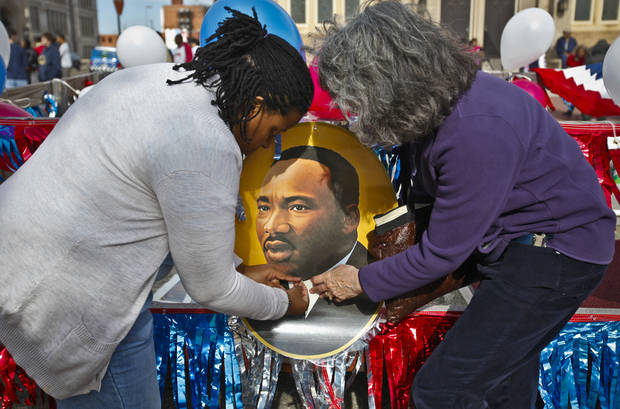 Jenice Brooks, left, works with Sheila Strawn to hang a photo of Martin Luther King Jr. on a float during Martin Luther King Jr. Day parade through downtown Oklahoma City on Monday, Jan. 16, 2012, in Oklahoma City, Okla. Photo by Chris Landsberger, The Oklahoman