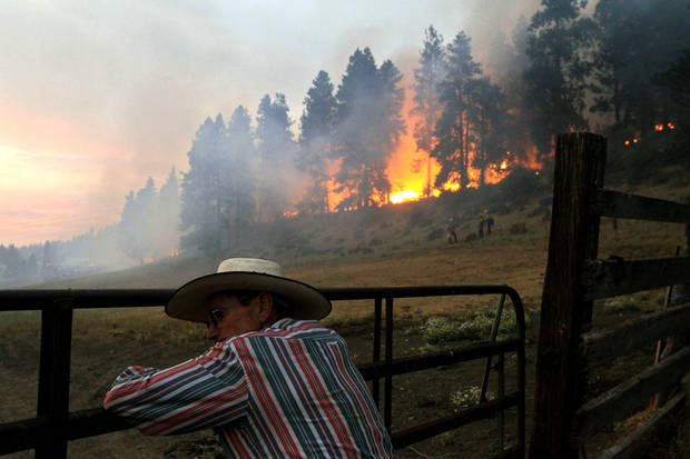 John Shea leans into a gate, exhausted, as a forest fire consumes the grounds around a friend's ranch Monday, Aug. 13, 2012, near Cle Elum, Wash. Shea heard the news, knew his friend was at work, and rushed over to his home to rescue livestock. Photo by Jordan Stead, The Seattle Times/AP