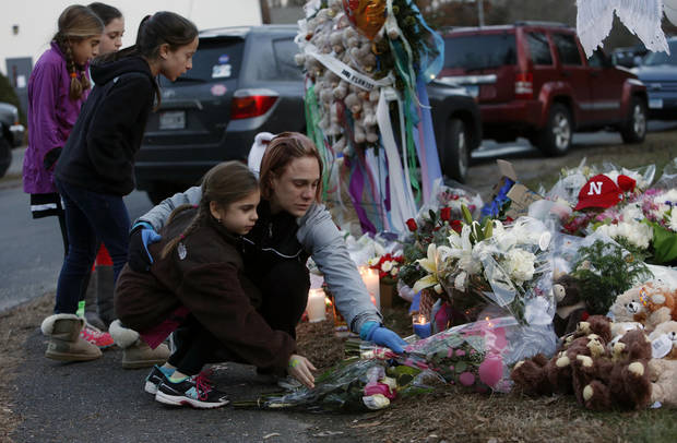 Mourners pay their respects at a memorial for shooting victims near Sandy Hook Elementary School, Saturday, Dec. 15, 2012 in Newtown, Conn.  A gunman walked into Sandy Hook Elementary School in Newtown Friday and opened fire, killing 26 people, including 20 children. (AP Photo/Jason DeCrow) ORG XMIT: CTJD121