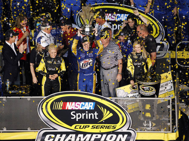 Brad Keselowski, center, holds up his trophy after winning the NASCAR Sprint Cup Series championship following an auto race at Homestead-Miami Speedway, Sunday, Nov. 18, 2012, in Homestead, Fla. Keselowski clinched the title after fellow contender Jimmie Johnson pulled out of the season finale because of a parts failure. Jeff Gordon won the race. (AP Photo/Wilfredo Lee)