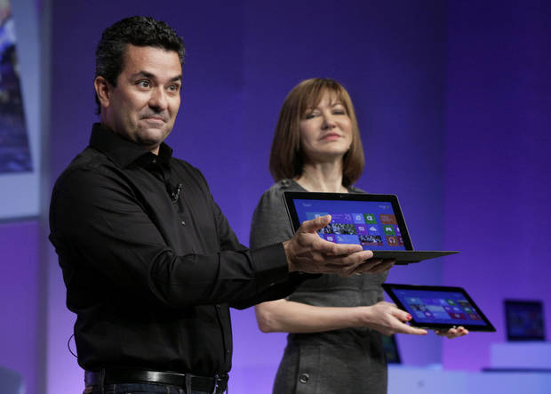 Mike Angiulo, corporate vice president of the Planning and PC Ecosystem team at Microsoft, shows the company�s Surface tablet computer Thursday at the launch of Microsoft Windows 8 in New York. He is accompanied by Microsoft Vice President Julie Larson-Green. AP Photo