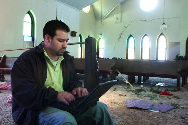 Tornado damage: Jeremy Alonzo, estimator for Scott's Construction Inc.  of Oklahoma City, estimates damage to the United Methodist church of Mulhall.  The church, built in 1894 sustained damage during monday's tornado and lost it's steeple.