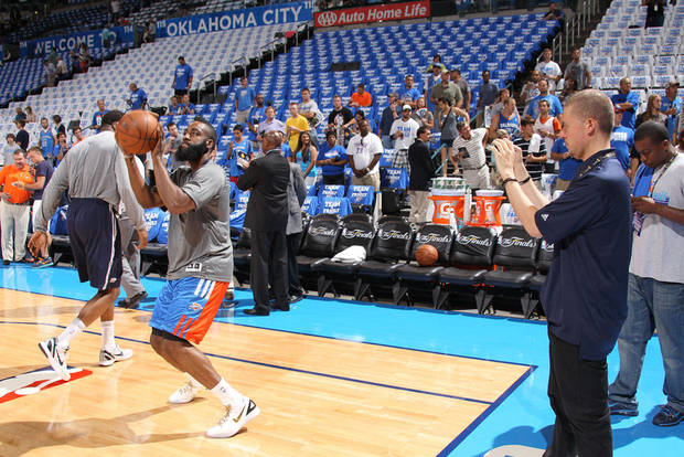 NBA�s Jim Poorten, right, uses his iPhone to take a picture of Oklahoma City�s James Harden before a recent game. Poorten will post it within minutes to one of the NBA�s social media sites like Twitter and Facebook. PHOTO BY NATHANIEL S. BUTLER / NBAE