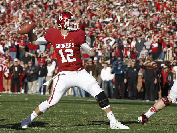   Oklahoma quarterback Landry Jones (12) throws against Oklahoma State in the first quarter of an NCAA college football game in Norman, Okla., Saturday, Nov. 24, 2012. (AP Photo/Sue Ogrocki)  