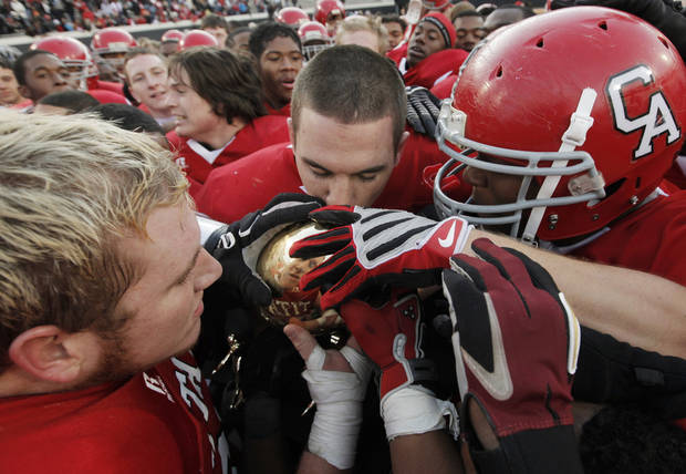 Carl Albert quarterback J.T. Realmuto, middle, kisses the championship trophy after the Class 5A state high school football championship game between Bixby and Carl Albert at Boone Pickens Stadium in Stillwater, Okla., Saturday, December 5, 2009. Carl Albert won, 21-7.  Photo by Nate Billings, The Oklahoman