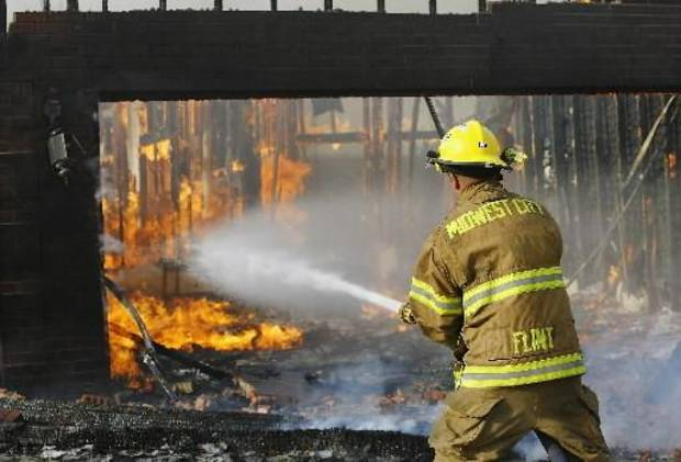 A Midwest City fireman fights flames in a garage in Midwest City Thursday. Photo by Jim Beckel