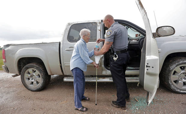Sgt. Clay Cline opens a bottle of water for Nancy Davis, 94, as she leaves her home that has been destroyed by a tornado for the second time near 149th and Drexel on Monday, May 20, 2013 in Oklahoma City, Okla.  Photo by Chris Landsberger, The Oklahoman
