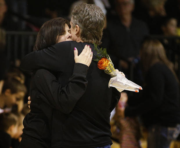 Seth Martin's mother Lisa Kinder hugs Cement basketball coach Mike Wynn before the start of a girls basketball game in Cement, Okla., Thursday, January 30, 2014.