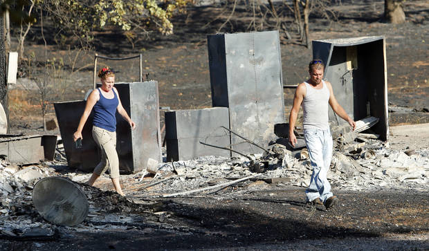 Regina and Sean Cox walk through what remains of the home and outbuilding of Regina's brother's mobile home as they see for the first time the damage from Friday's wildfire on Saturday, Aug. 4, 2012, in Slaughterville, Okla.  Photo by Steve Sisney, The Oklahoman