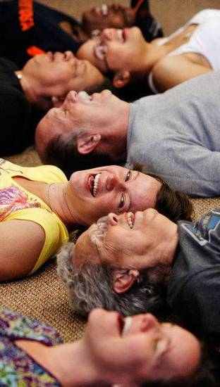 Near the end of the session, participants lie on their backs to laugh and do their breathing during a laughing yoga class led by Ellen Mercer. Photo by Jim Beckel, The Oklahoman <strong>JIM BECKEL</strong>